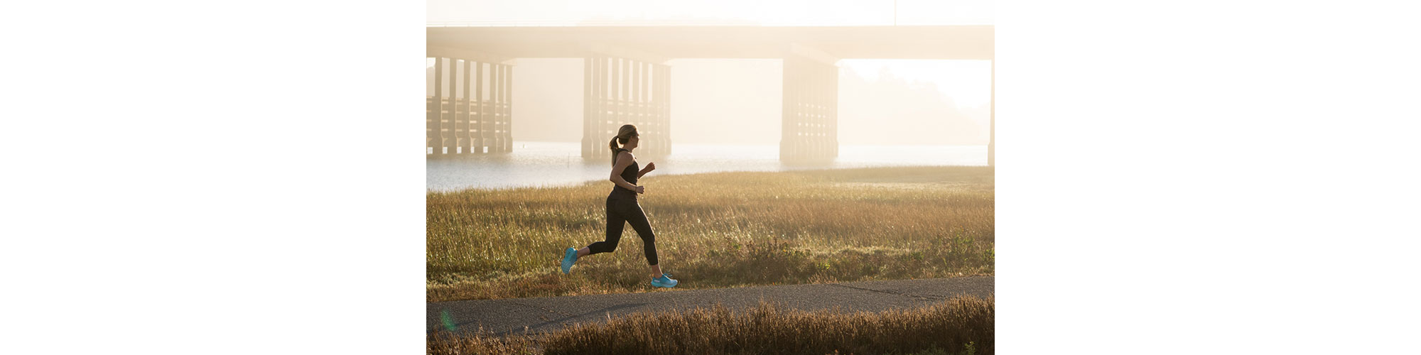 A woman running in the early morning on a trail near a bridge and river.