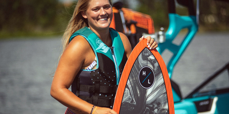 A woman holding up a wakeboard with a life jacket over swimwear.