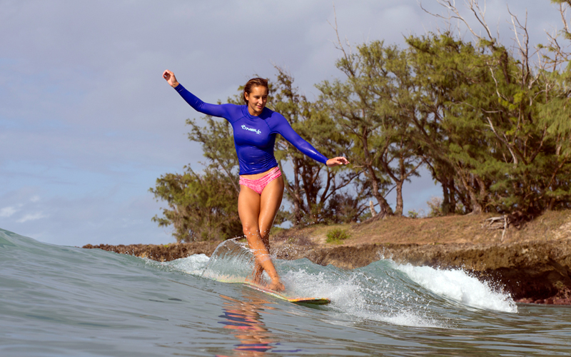 A woman riding a wike in a blue rashguard top and bikini bottom.